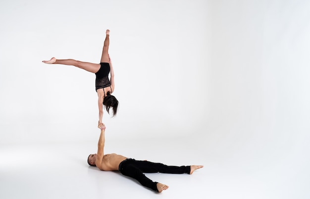 Duo van mannelijke en vrouwelijke acrobaten tonen truc van hand tot hand, geïsoleerd op wit
