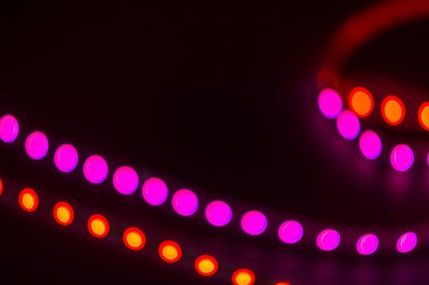 Duotoon bokeh abstracte lijnen. rode en paarse wazige lichten op zwart.