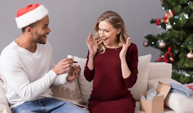 Dure gift. goed uitziende vrolijke jongeman die een doosje vasthoudt en de ring laat zien aan zijn vriendin terwijl hij haar een cadeau geeft