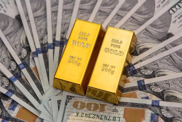 Dure goudstaaf die op dollarbiljetten ligt. geld concept opslaan