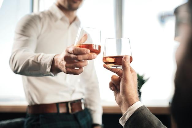 Dure whisky. sluit omhoog van twee glazen van de zakenmanholding met dure whisky die na het werk drinkt