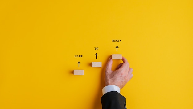 Durf het bord te beginnen dat boven de treden van houten pinnen is geschreven. over gele achtergrond.