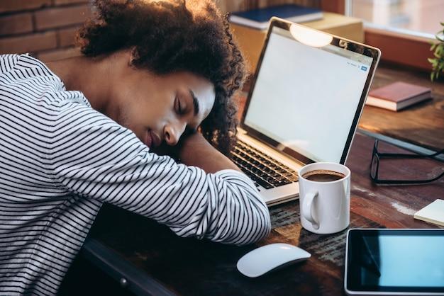 Dutje. zijaanzicht van een jonge afrikaanse man die op een laptop slaapt met gesloten ogen terwijl hij op zijn werkplek zit