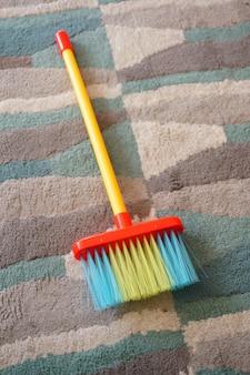 Duw een bezem van verschillende kleuren op een veelkleurig tapijt