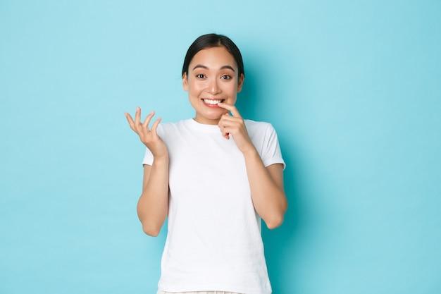Dwaas en schattig lachend aziatisch meisje in wit t-shirt, geamuseerd en verbaasd kijkend, schouderophalend en bijtende vinger koket, staande blauwe achtergrond verward en besluiteloos.