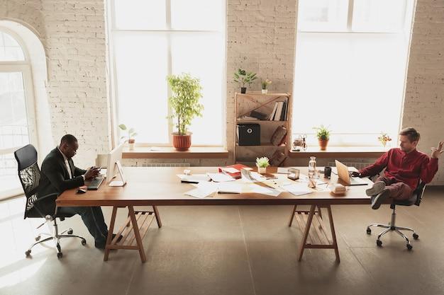 Dwaas rond voor zijn baas. blanke werknemer, manager die op kantoor probeert te werken.