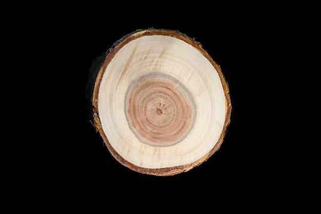Dwarsdoorsnede van de boomstam van de kersenboomgaard die jaarringen toont die op zwarte achtergrond worden geïsoleerd.