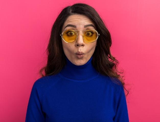 Dwaze jonge mooie vrouw die een zonnebril draagt die naar de voorkant kijkt en een visgezicht maakt dat op een roze muur wordt geïsoleerd