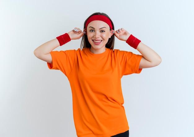 Dwaze jonge sportieve vrouw die hoofdband en polsbandjes draagt die het kijken glimlachen makend grote oren geïsoleerd