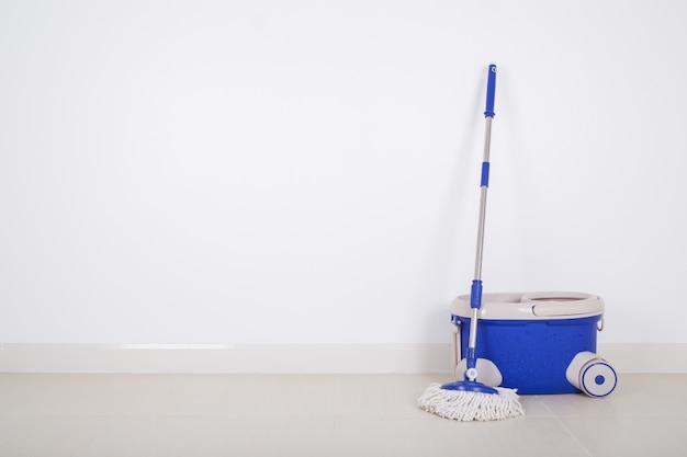 Dweil en blauwe emmer op vloer en muur achtergrond