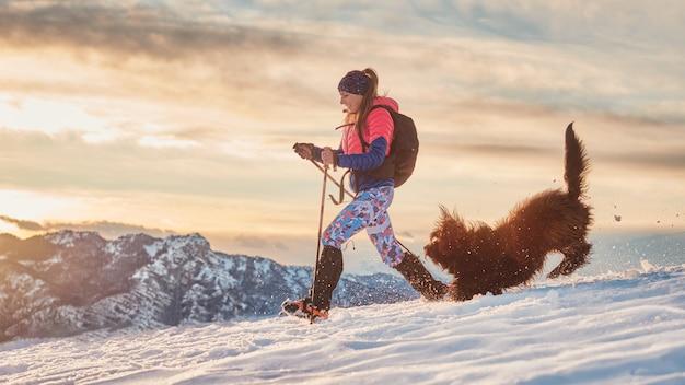 Dwergpapegaaienmeisje en haar hond spelen in de sneeuw tijdens een winterwandeling