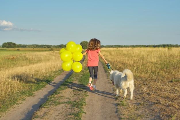 Dynamisch openluchtportret van lopend meisje met witte hond en gele ballons