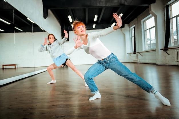 Dynamische bewegingen. mooie roodharige leraar in blauwe spijkerbroek en een student die zwarte korte broek draagt die zich actief voelt