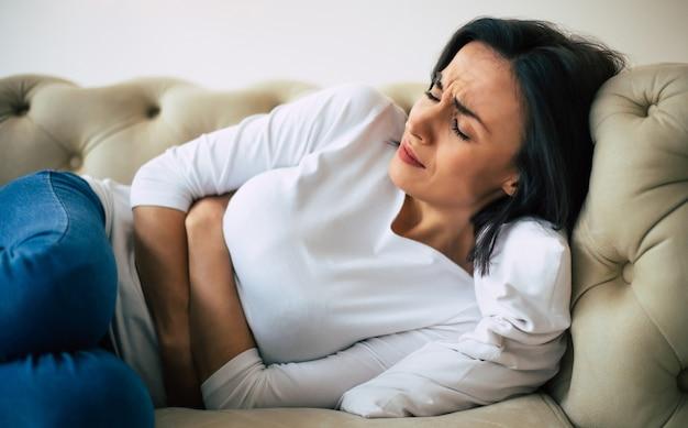 Dysmenorroe. close-up foto van een vrouw, die op haar bank ligt en haar buik vasthoudt met een lijdende gezichtsuitdrukking.