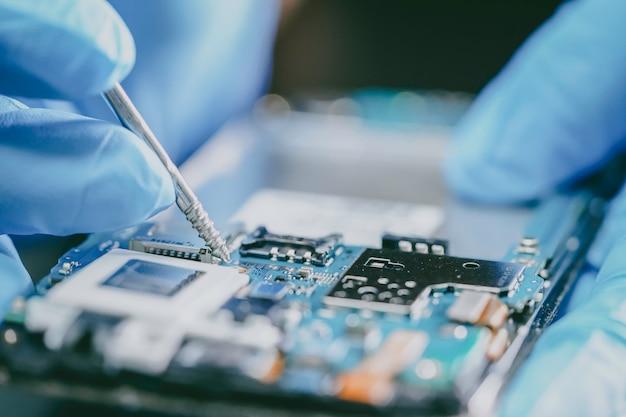 E-afval, technicus die binnenkant van mobiele telefoon herstelt door ijzer te solderen.