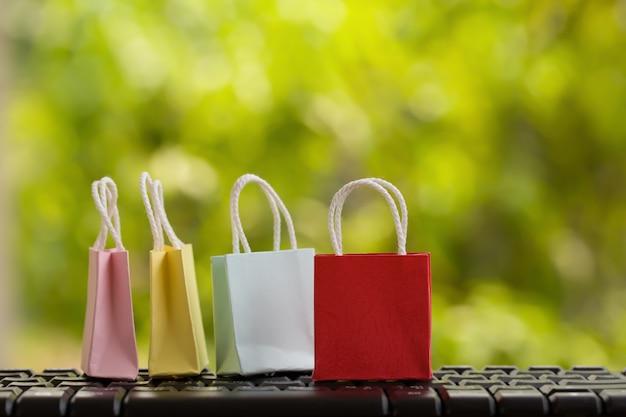 E-commerce concept. : gekleurde papieren boodschappentassen met op notebook-toetsenbord in de natuurlijke groene natuur. internationale vracht- of verzendservice voor online winkelen