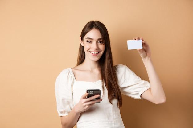 E-commerce concept. glimlachende vrouw die plastic creditcard toont tijdens het online winkelen op de mobiele telefoon, die zich tegen een beige achtergrond bevindt.