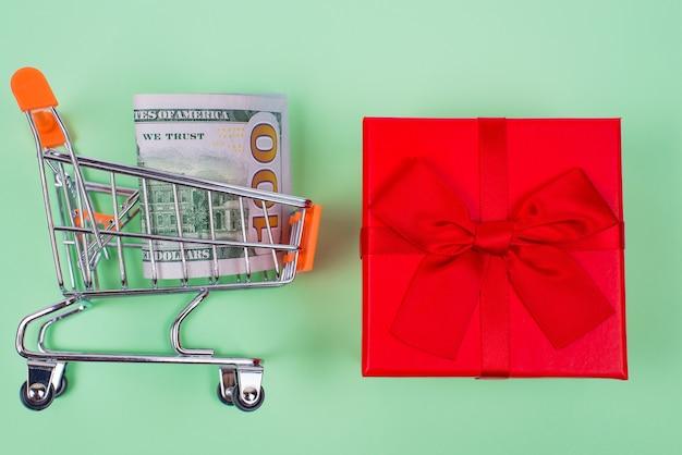 E-commerce concept laatste kans verkoop verjaardag. top boven hoge hoek plat lag close-up foto van helder lint klein pakket en trolley met 100 dollar geïsoleerd op pastel groene achtergrond
