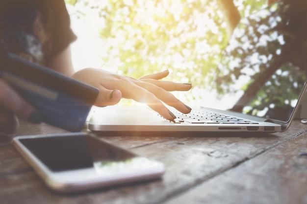 E-commerce concept. vrouw met behulp van laptop en creditcard voor online winkelen bij coffee shop.