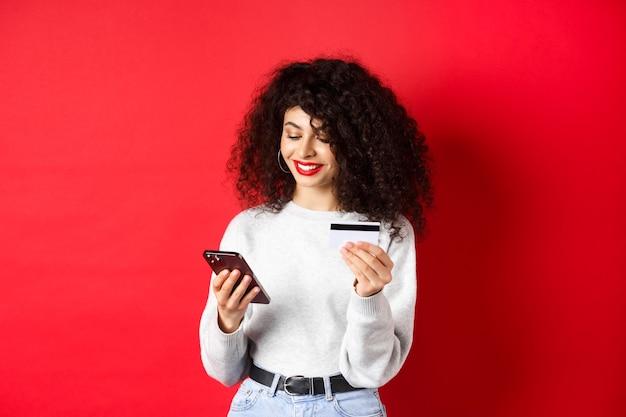 E-commerce en online winkelconcept. aantrekkelijke blanke vrouw die voor aankoop op internet betaalt, smartphone en creditcard vasthoudt, rode achtergrond