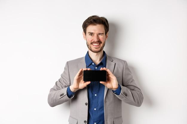 E-commerce en online winkelconcept. brutaal mannelijk model in pak knipogen en tonen leeg smartphonescherm, glimlachend gelukkig op camera, witte achtergrond.