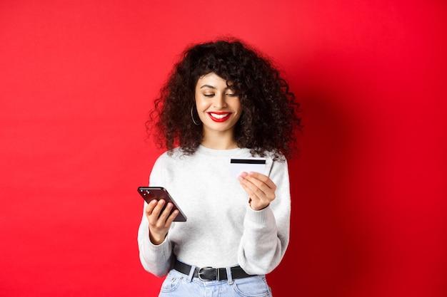 E-commerce en online winkelconcept. jonge moderne vrouw betalen met creditcard, aankoop met smartphone, staande op rode achtergrond.