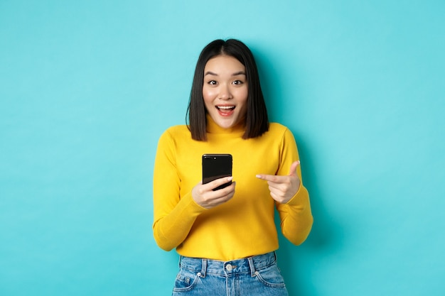 E-commerce en online winkelconcept. verrast aziatische vrouw demonstreren smartphone-app, internetkortingen, wijzende vinger op mobiele telefoon, blauwe achtergrond.