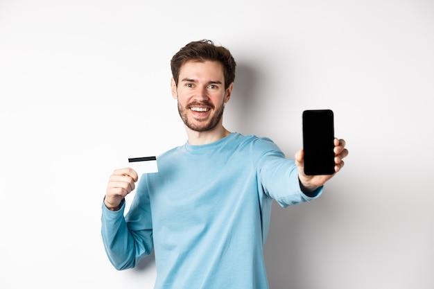 E-commerce en winkelconcept. glimlachende blanke man met plastic creditcard en leeg smartphonescherm, online app aanbevelend, witte achtergrond