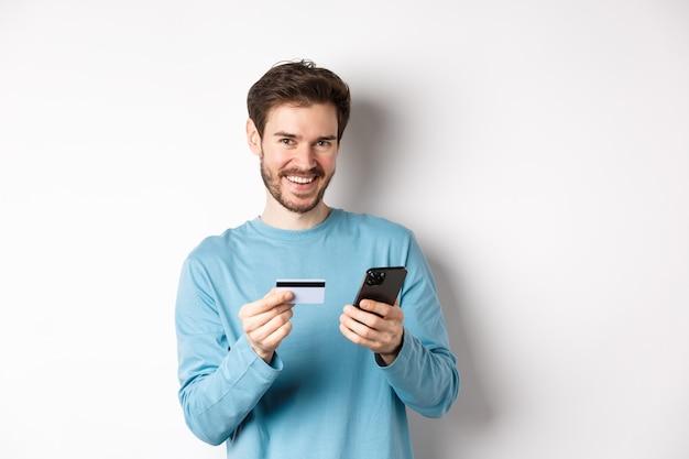 E-commerce en winkelconcept. glimlachende jonge man die online betaalt met plastic creditcard en smartphone, staande op een witte achtergrond