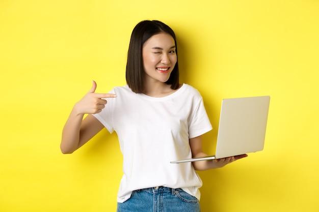 E-commerce en winkelconcept. knap aziatisch meisje knipogen naar de camera, glimlachend en wijzende vinger een laptop, iets laten zien, staande over geel.