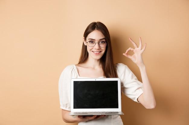 E-commerce. glimlachende jonge vrouw in glazen die goed teken en laptop scherm tonen, die internetpromo aanbevelen, die zich op beige achtergrond bevindt.