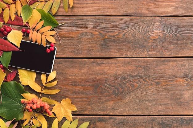 E-commerce herfstbladeren houten muur concept. smartphone-technologie.