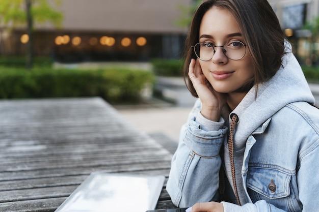 E-learning, onderwijs en mensenconcept. close-up portret dromerige verleidelijke vrouw in spijkerjasje en bril, overweegt de vroege mooie lentedag, zitbank met laptop en mobiele telefoon glimlachen.