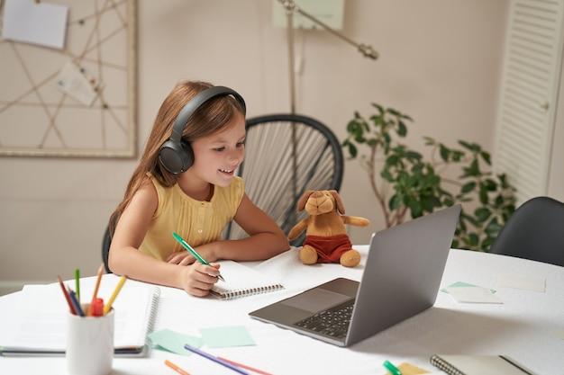 E-learning systeem slim klein kaukasisch meisje in koptelefoon zittend aan tafel met laptop en