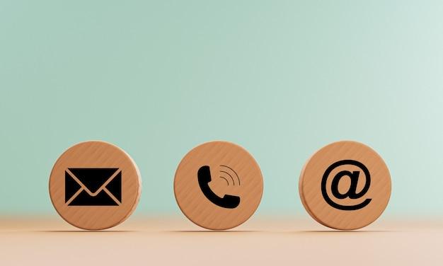 E-mailadres, telefoonnummer en letterpictogrammen printscherm op cirkel houten blok op tafel voor webpagina zakelijk contact en klantenserviceconcept door 3d-rendering.