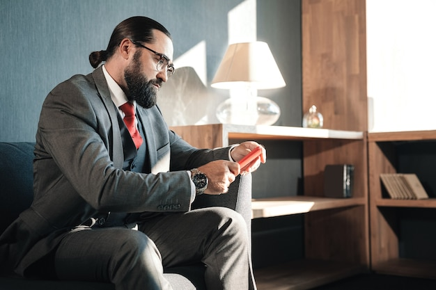 E-mails lezen. ernstige bebaarde zakenman die het druk heeft tijdens het lezen van e-mails op zijn rode telefoon