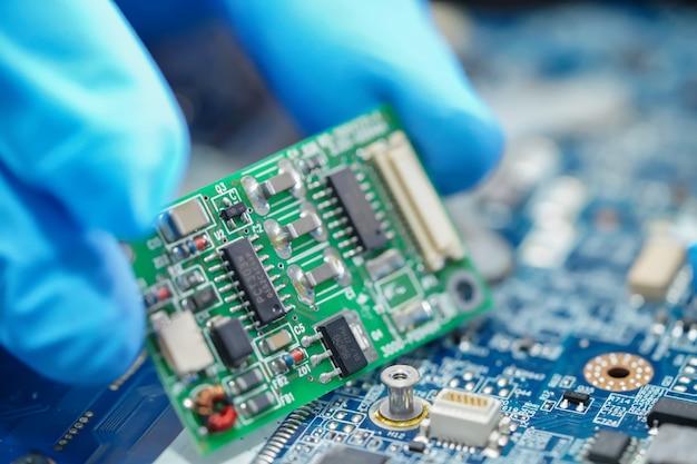 E-waste, technicus die binnen van harde schijf herstelt.