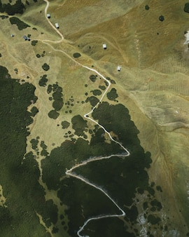 Eagle-eye verticaal bijschrift van een smalle weg op de top van de heuvel
