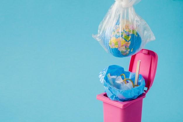 Earth globe ligt in de prullenbak. de wereldbol ligt in een hoop plastic
