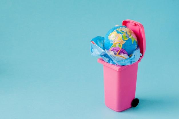 Earth globe ligt in de prullenbak. plastic vervuiling concept