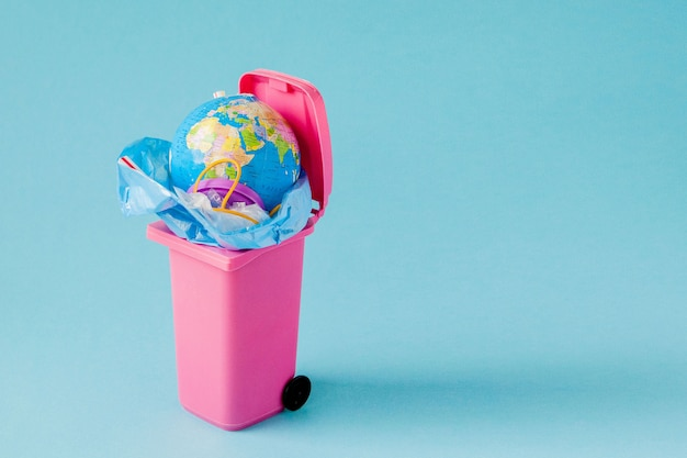 Earth globe ligt in de prullenbak