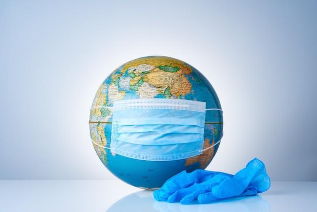 Earth globe met medisch masker naast een paar chirurgische handschoenen