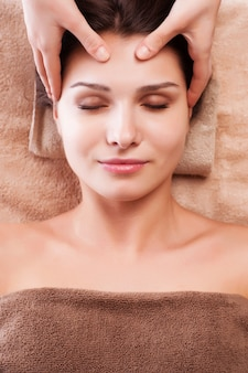Eautiful jonge ontspannen vrouw geniet van het ontvangen van gezichtsmassage bij kuuroordsalon