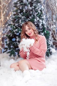 Eautiful meisje in een roze trui zit in de kerstversiering met kunstmatige sneeuw