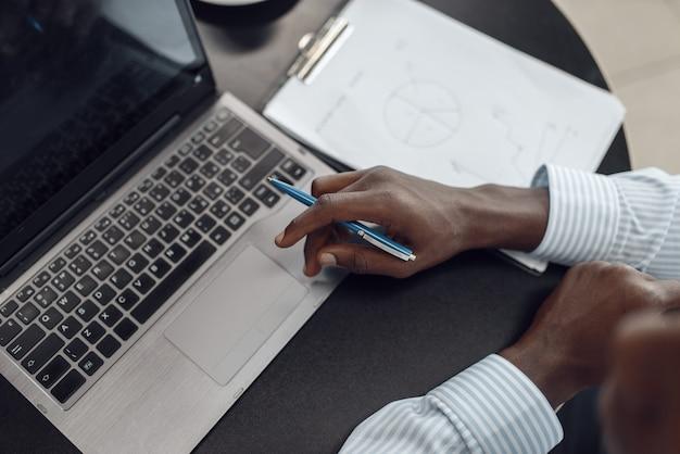 Ebony zakenman bezig met laptop in kantoor, bovenaanzicht. succesvolle ondernemer op zijn werkplek, zwarte man in formele kleding