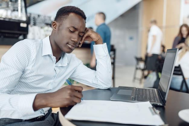 Ebony zakenman die op laptop in bureau werkt. succesvolle zakenman op zijn werkplek, zwarte man in formele kleding