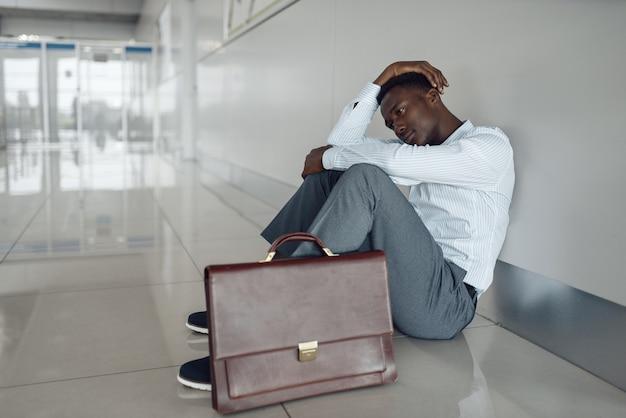 Ebony zakenman met werkmap zittend op de vloer in de gang van het kantoor. moe zakenman ontspannen in gang, zwarte man in formele kleding