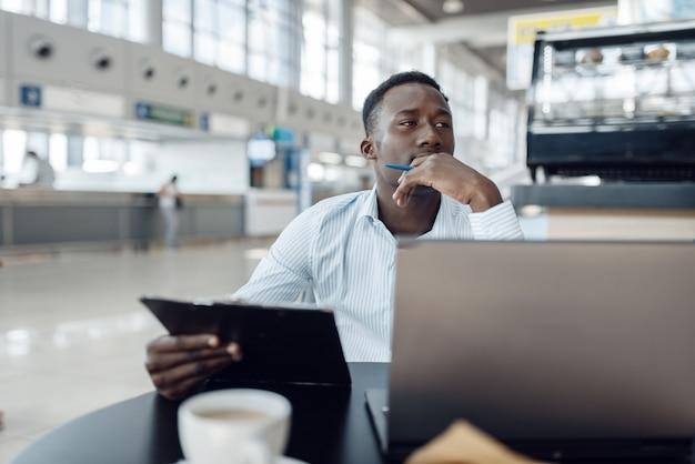 Ebony zakenman zit op laptop in autodealer. succesvolle zakenman op motorshow, zwarte man in formele kleding, autoshowroom