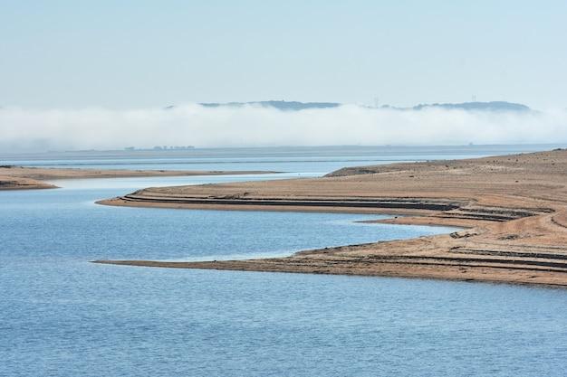 Ebro rivier moeras met wolk van mist op de achtergrond en strand op de voorgrond