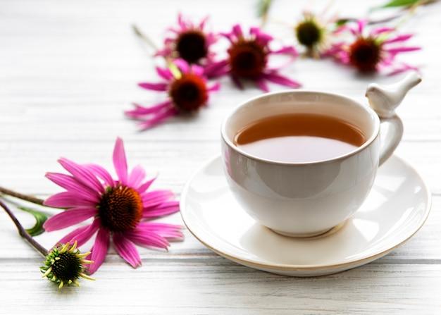 Echinacea-thee met verse bloemen. kopje thee op een tafel